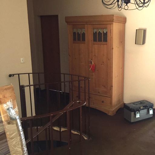 Wendeltreppe mit altem Anstrich und Teppich drumherum