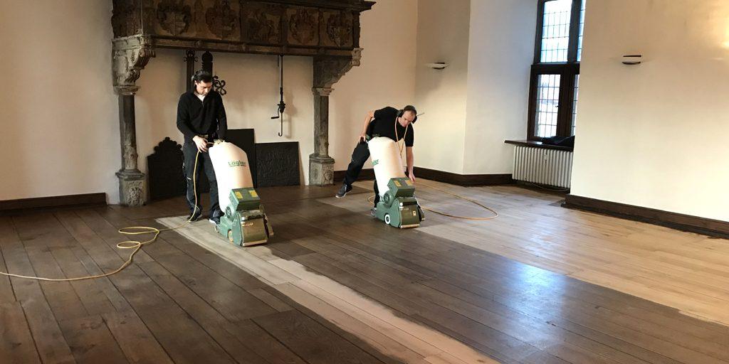 Schmutz abschleifen, um denkmalgeschützte Böden zu renovieren.