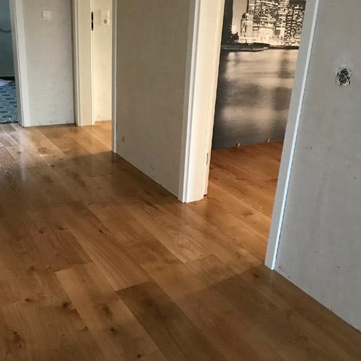 Boden renovieren: Massive Holzdielen aus Eiche kleben auf Estrich.