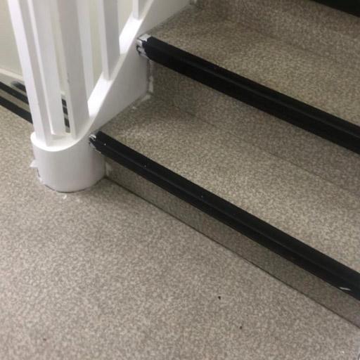 Treppe vor der Treppenrenovierung / Teppensanierung: Belag mit grauem PVC/Vinyl