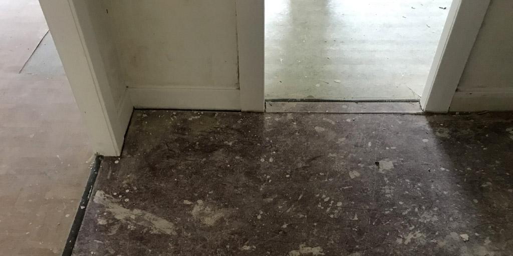 Verschiedener Belag aus PVC klebt auf den Dielen.
