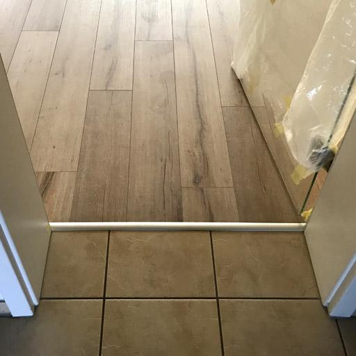 Der Anschluss zur Tür und dem Fliesenboden ist ohne Teppich unter dem Laminat hergestellt.